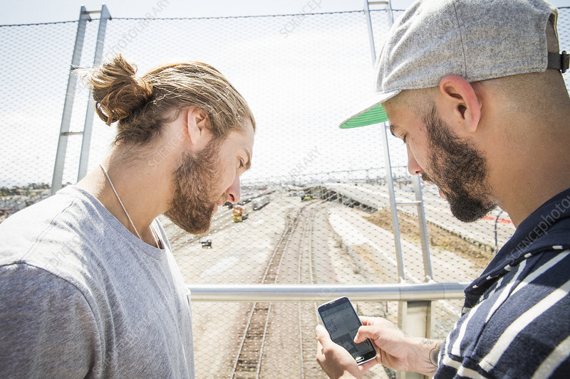 Two young men using a mobile phone