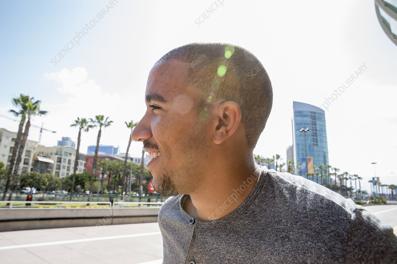 Smiling young man standing in a street
