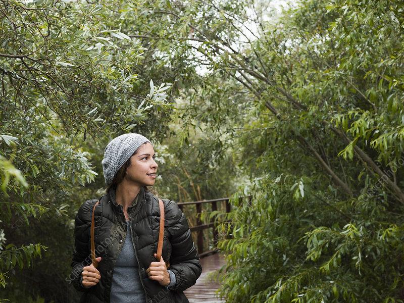 Young woman walking through woodland