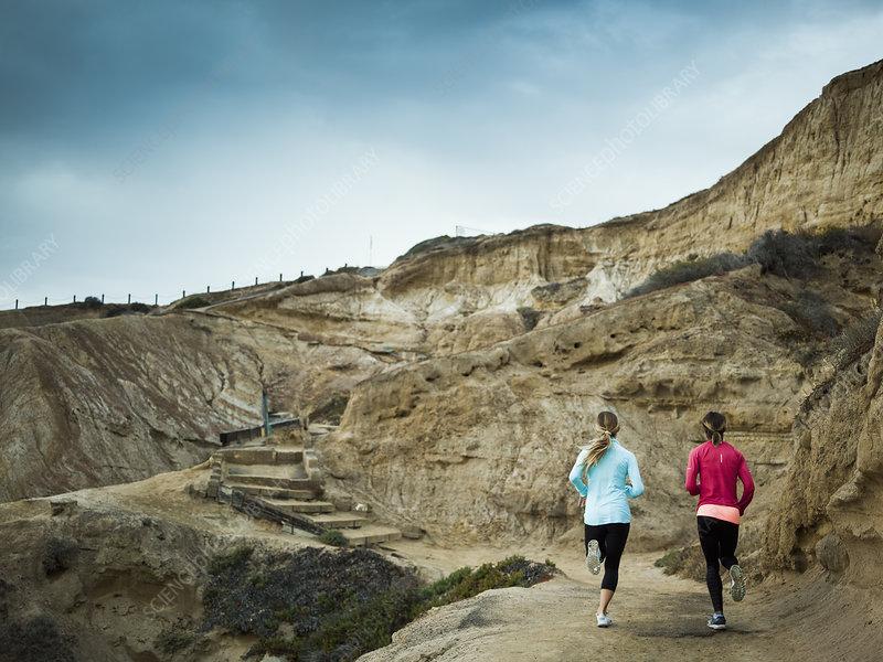Two women jogging along a quarry trail