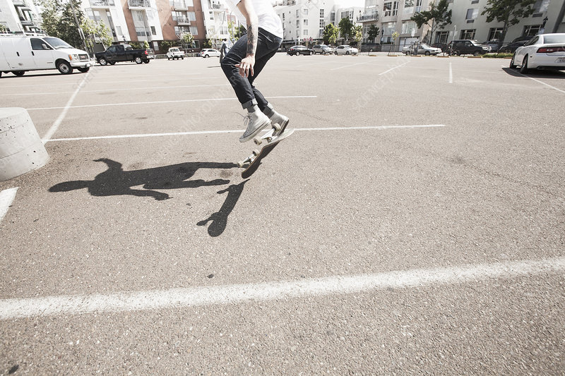 Young man skateboarding in a car park