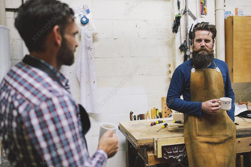Two craftsmen in pipe organ workshop