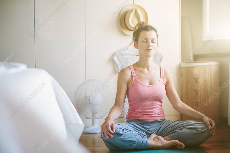 Woman in yoga lotus position in bedroom