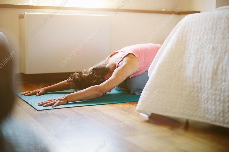 Woman in yoga position on bedroom floor