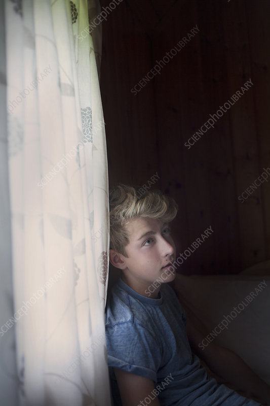 Pensive teenage boy by curtains