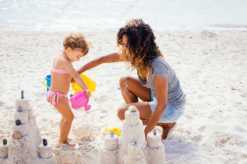 Mother and daughter building sandcastle