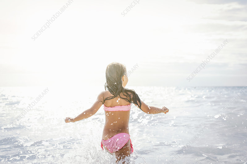 Girl running and splashing in sea