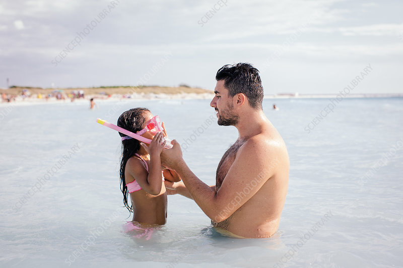 Father teaching daughter to snorkel
