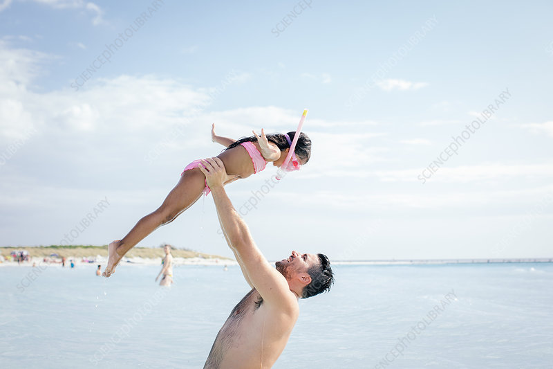 Father holding up snorkeler daughter