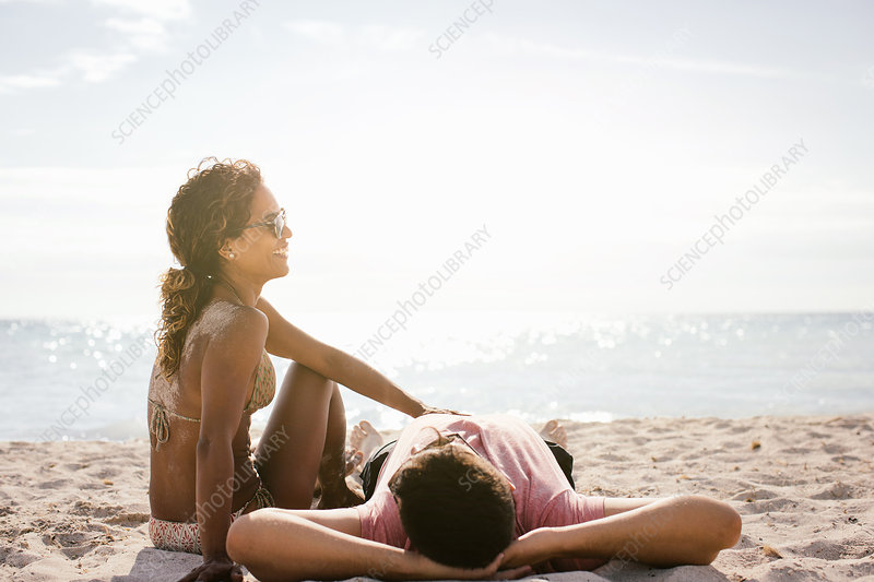 Couple on beach sunbathing
