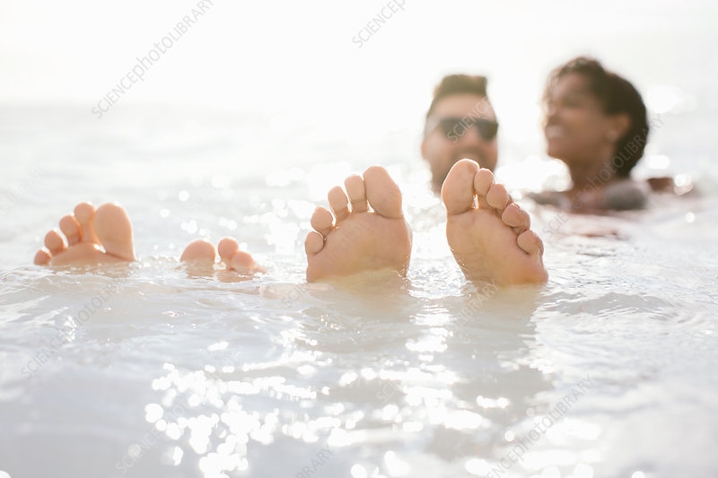 Couple with feet up in sea