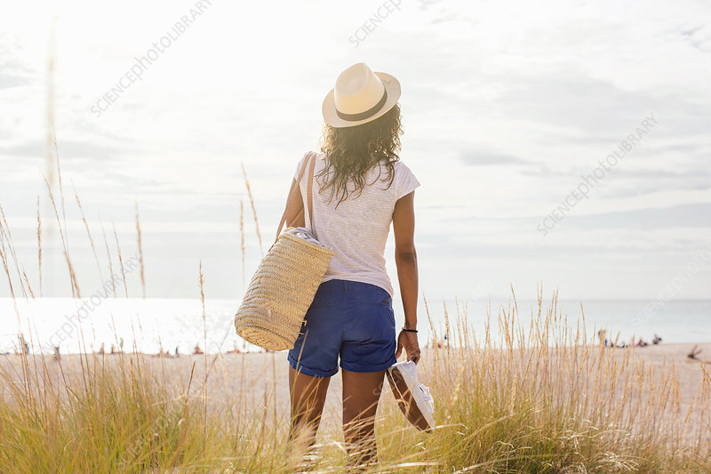 Young woman with beach bag in dunes