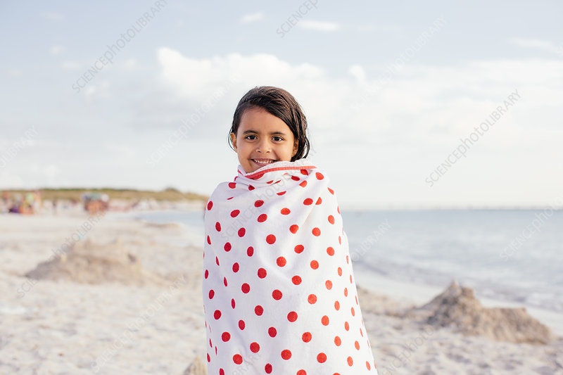 Girl wrapped in spotted towel on beach