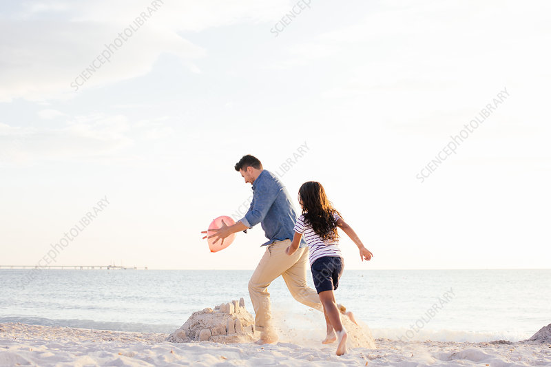Girl chasing father for balloon on beach