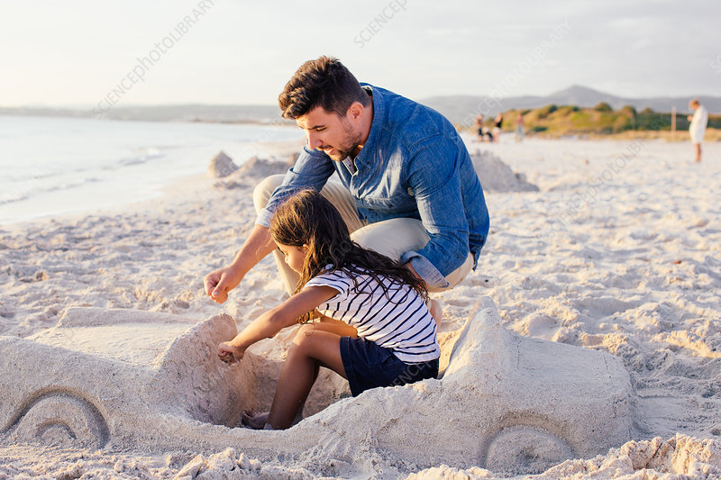 Girl and father with car sandcastle