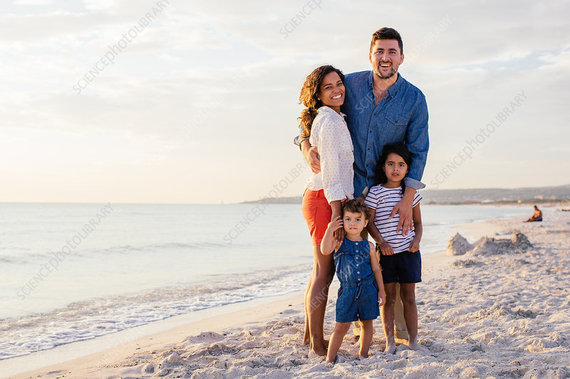 Smiling couple with two girls on beach