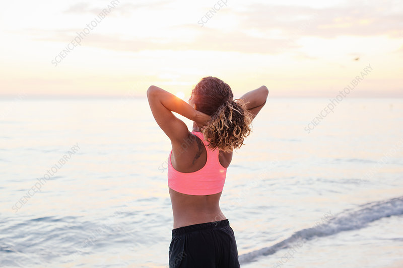 Woman stretching on beach at sunset