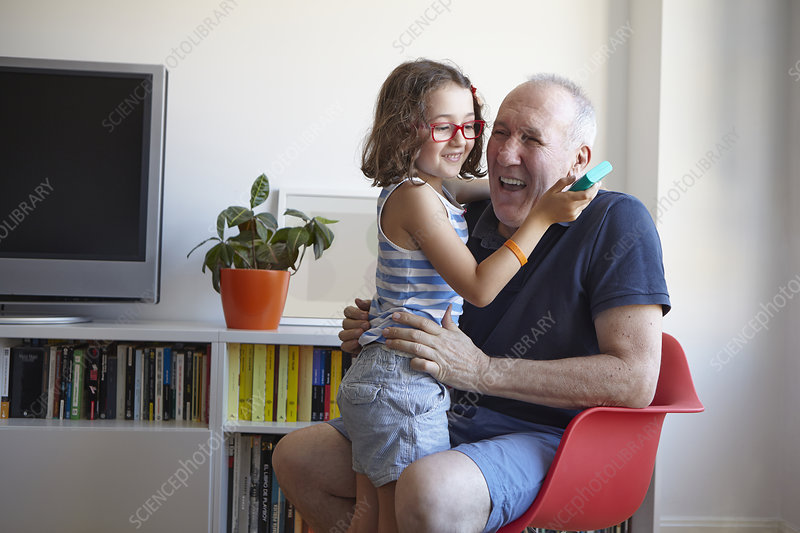 Girl and grandfather playing video game
