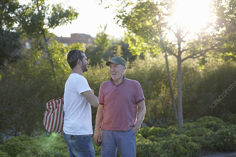 Mid adult man talking to senior man