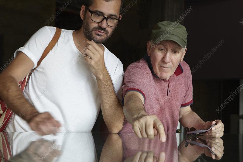 Man looking at senior man pointing