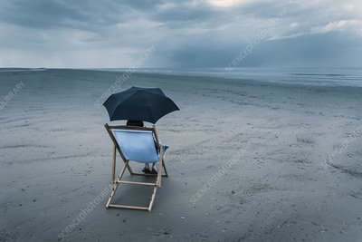 Woman sitting on stormy beach