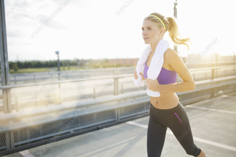 Young woman jogging with towel