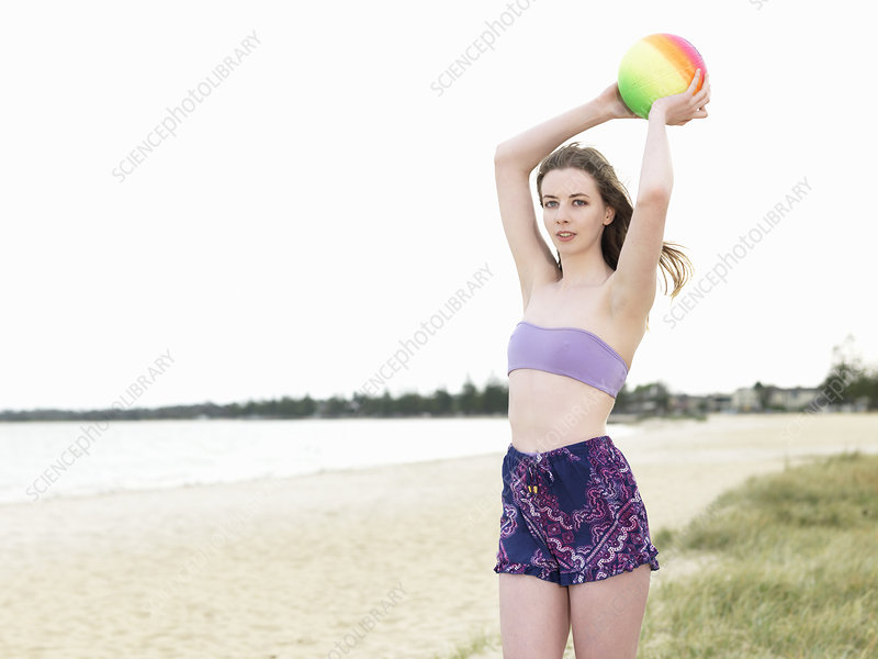 Young woman throwing beach ball