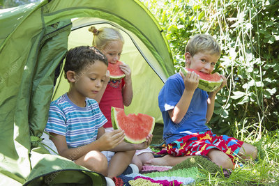 Children eating watermelon slices in tent