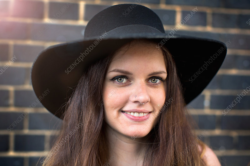 Young woman with hat and nose ring stud