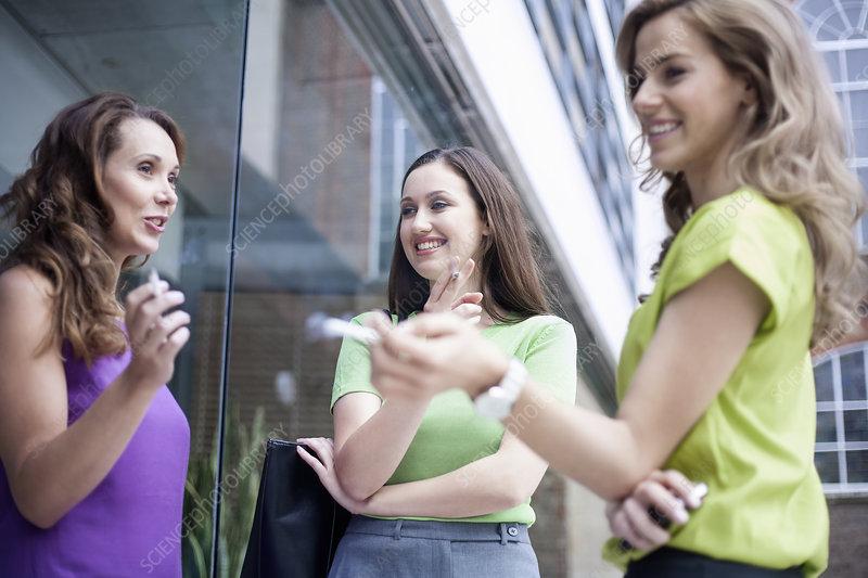 Women smoking cigarettes outside