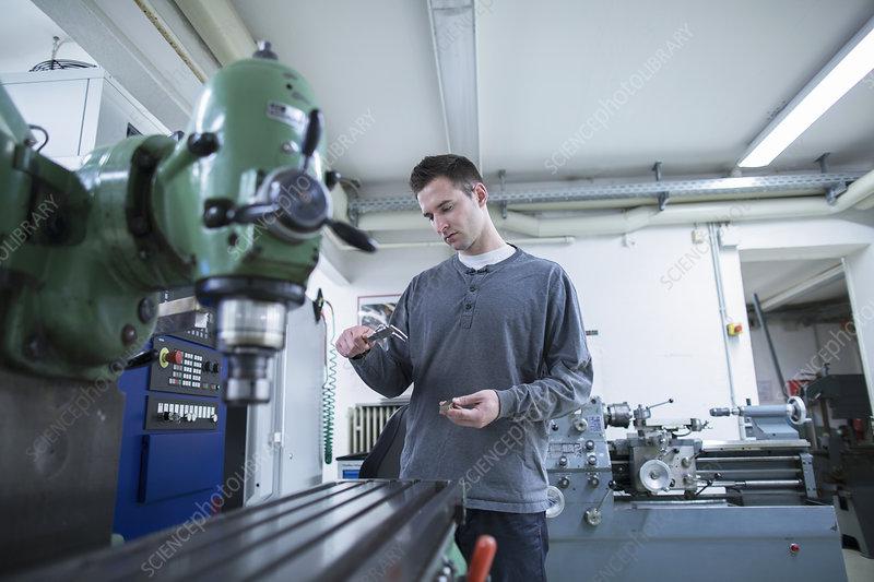 Technician using vernier caliper