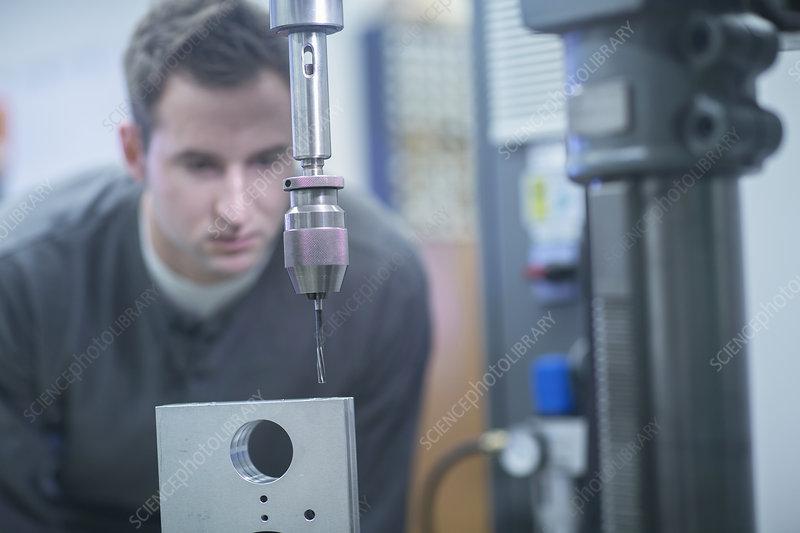 Technician checking metal drill machine