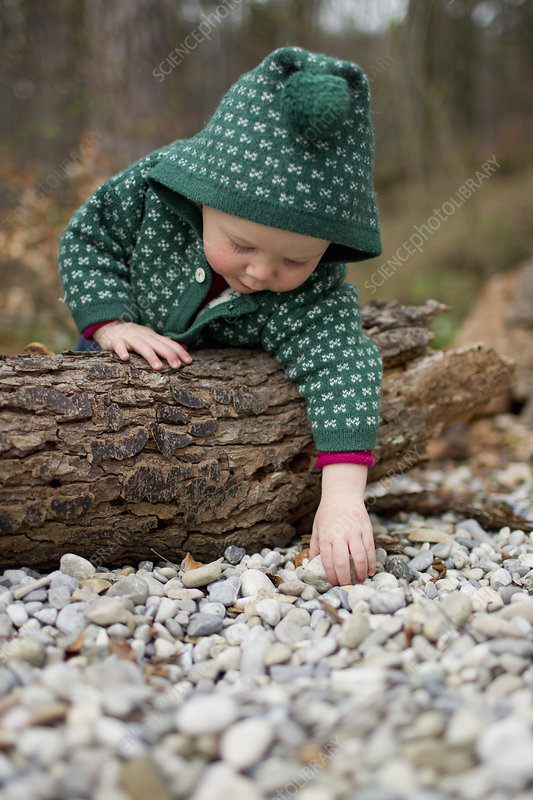 Girl leaning over tree trunk