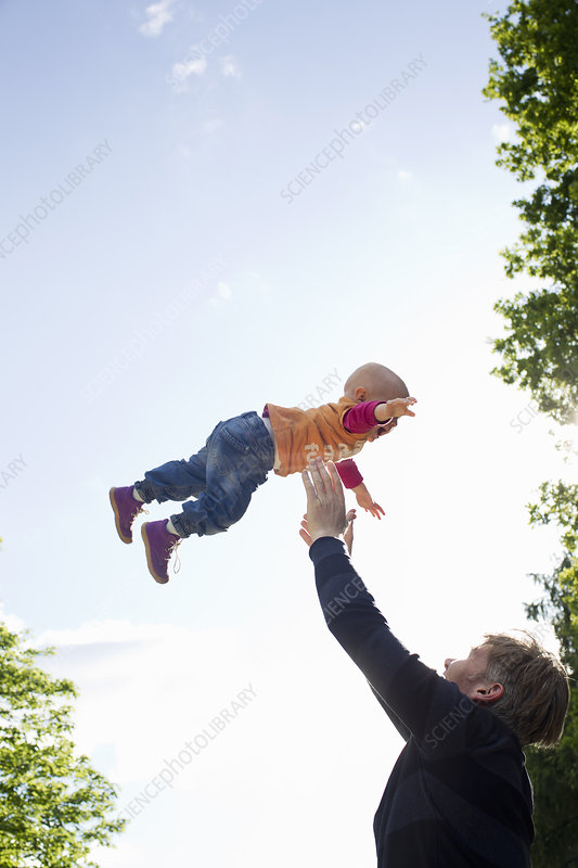Father throwing baby daughter mid air