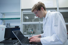 Male scientist typing on laptop in lab