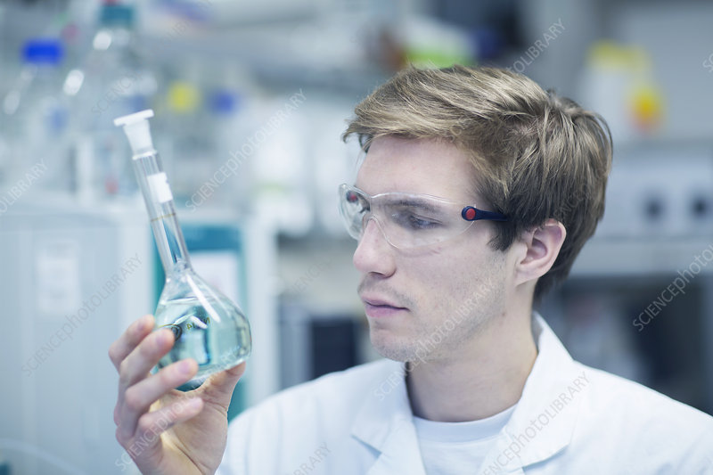Scientist holding up and looking at flask
