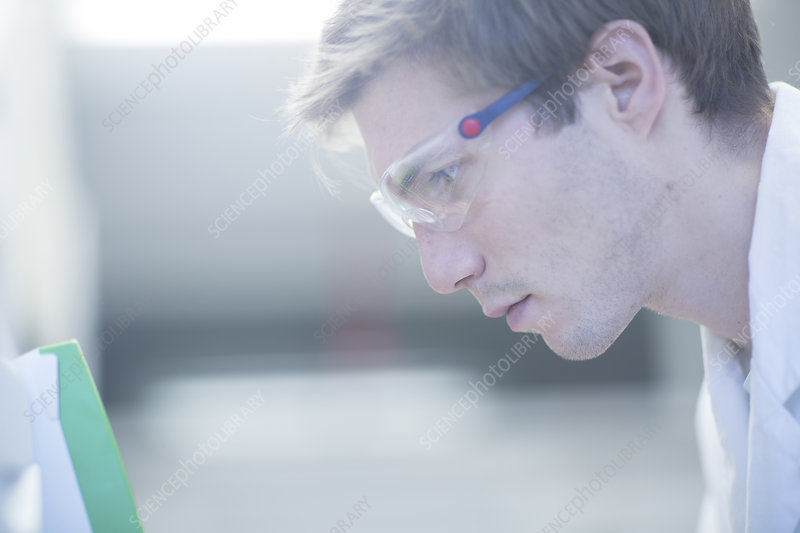 Male scientist reading papers in lab