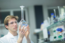 Male scientist holding up flask in lab