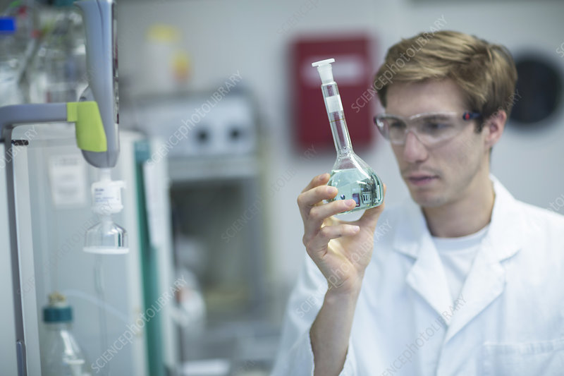 Male scientist looking at flask in lab
