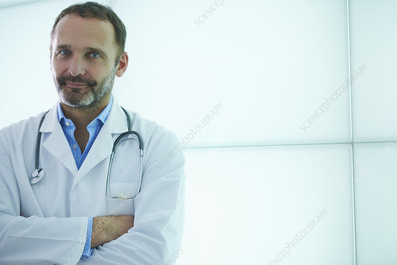 Doctor posing against backlit wall panel