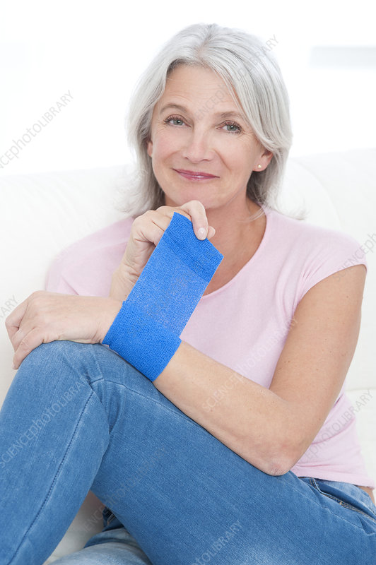 Woman putting bandage on wrist