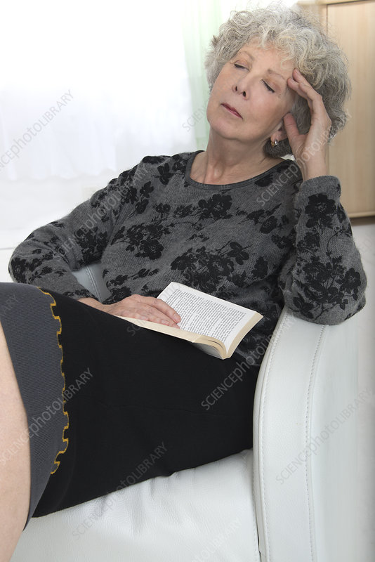 Woman asleep on a chair with a book