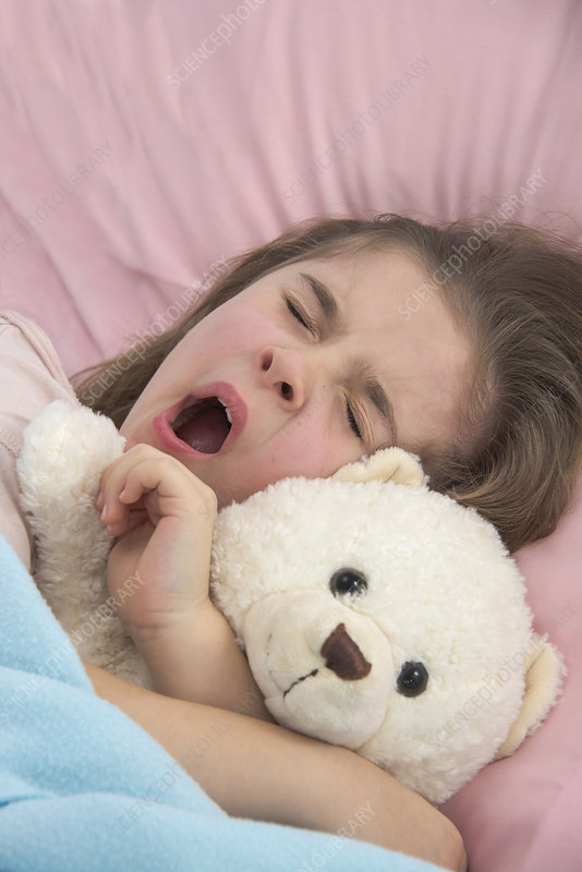Girl yawning in bed holding teddy bear