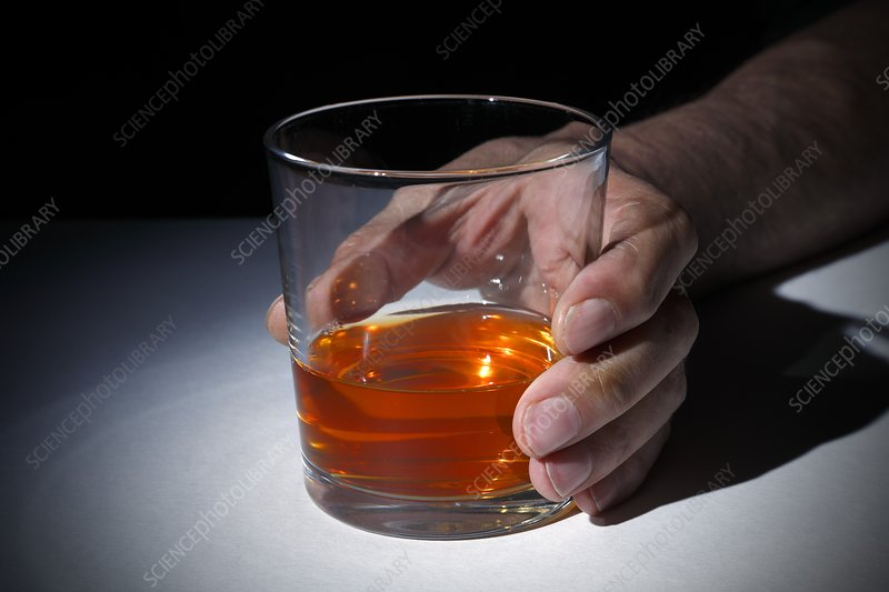 Person holding a glass of whisky