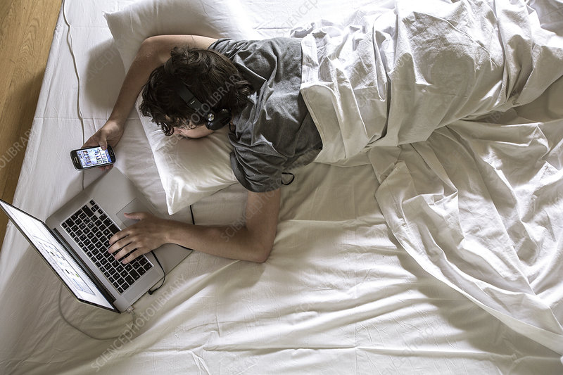 Man lying in bed using laptop and phone