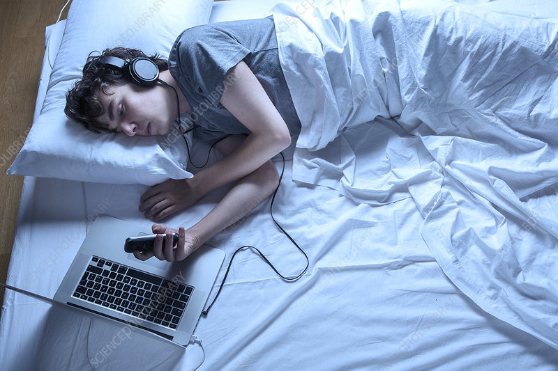 Man asleep in bed with laptop and phone