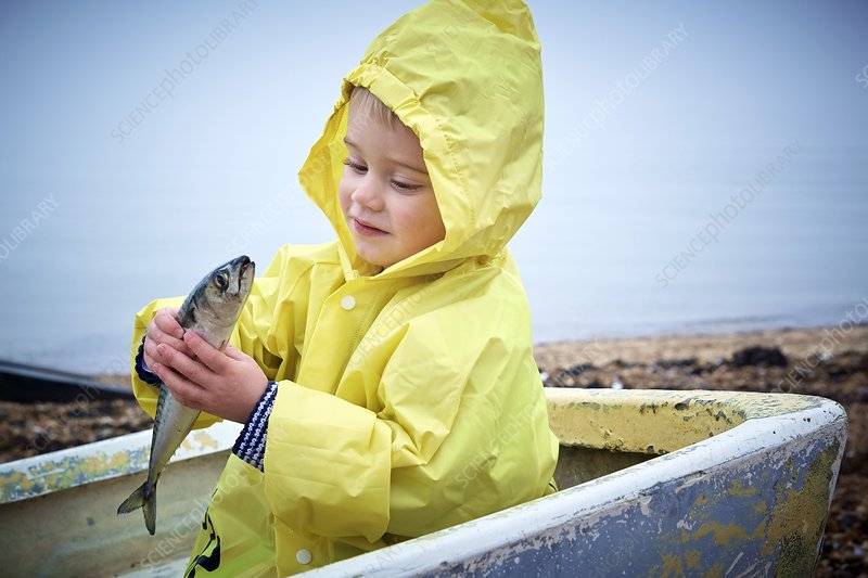 Boy wearing raincoat holding a mackerel