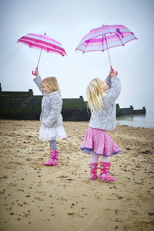 Two girls on beach holding umbrellas