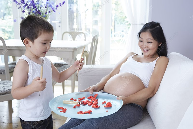 Pregnant woman playing with son