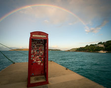 Rainbow over a red phone booth by water